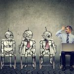 Man sits next to 3 robots